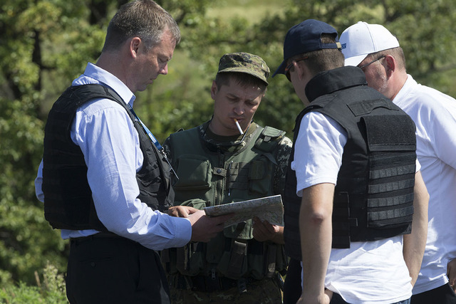Alexander Hug, deputy head of the OSCE mission to Ukraine, left, his colleagues and a pro-Russian rebel, 2nd left, examine a map as they try to estimate security conditions outside the city of Don ...