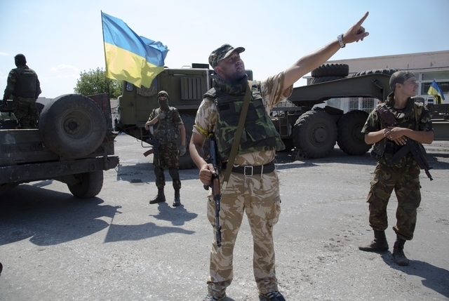 An Ukrainian government army's soldier gestures at a check-point in the village of Debaltseve, Donetsk region, eastern Ukraine Thursday, July 31, 2014. (AP Photo/Dmitry Lovetsky)