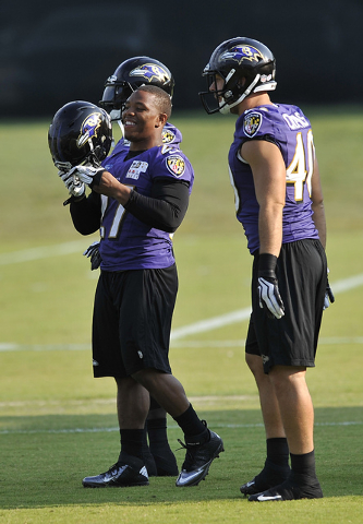Baltimore Ravens running back Ray Rice, left, smiles as he puts on his helmet next to Shaun Chapus, right, during NFL football training camp practice, Thursday, July 31, 2014, in Owings Mills, Md. ...