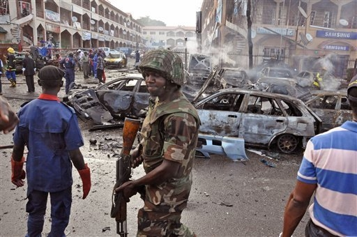 In this Wednesday, June, 25, 2014, file photo, a Nigerian soldier, center, walks, at the scene of an explosion in Abuja, Nigeria. A car bomb exploded in a market in Nigeria's northeastern city of  ...