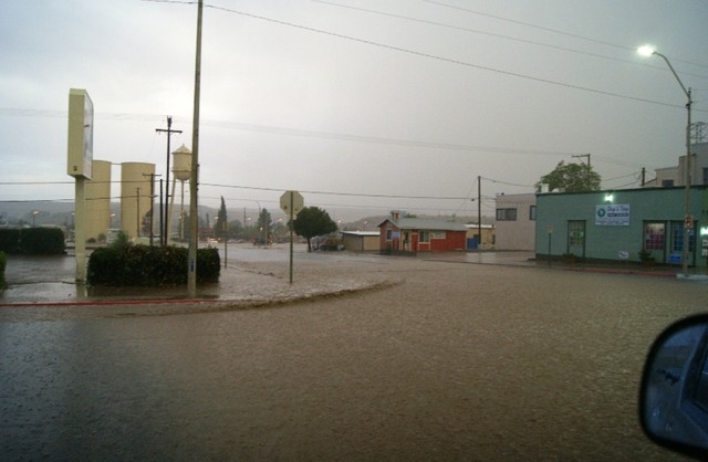 Water runs through the intersection at Fifth and Beale Streets in Kingman, Ariz. on Monday, July 14, 2014 during a fierce monsoon season thunderstorm. The Kingman Fire Department and Northern Ariz ...