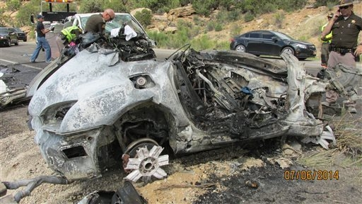 This photo provided by the Utah Department of Public Safety, shows a damaged vehicle from a head-on collision, Sunday July 6, 2014, in southern Utah.  A van carrying five people was trying to pass ...