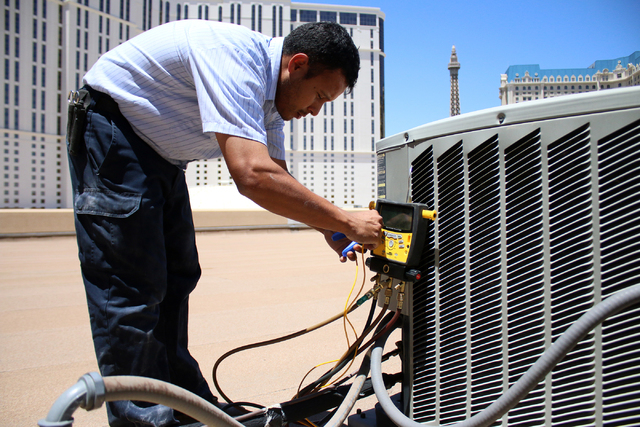 Air conditioner repairmen, Peter Almanza of Cal Air works on an air conditioning unit on the roof of Planet Hollywood Miracle Mile Shops on Tuesday, July 1, 2014. Almanza performed maintenance on  ...