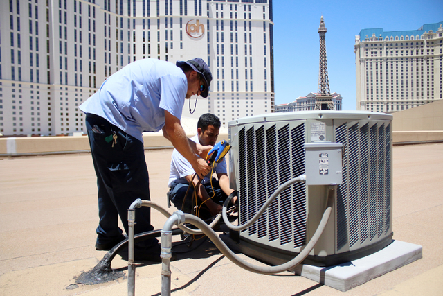 Air conditioner repairmen, Peter Almanza, right, and Sterling Broome of Cal Air work on an air conditioning unit on the roof of Planet Hollywood Miracle Mile Shops on Tuesday, July 1, 2014. They p ...