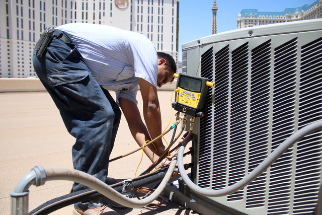 Air conditioner repairman, Peter Almanza of Cal Air works on an air conditioning unit on the roof of Planet Hollywood Miracle Mile Shops on Tuesday, July 1, 2014. Almanza performed maintenance on  ...