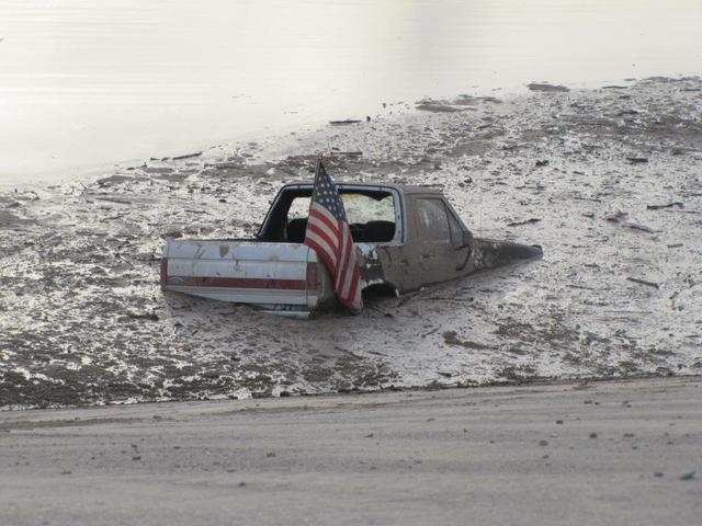 A truck is stuck in a flooded detention basin Sunday, July 6, 2014, in Las Vegas. The male driver of the truck was helped out by a friend and was not hurt in the Sunday evening incident. (AP Photo ...