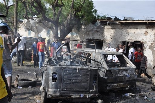 People look at damaged vehicles, at the scene of a car bomb explosion, at the central market, in Maiduguri, Nigeria, Tuesday, July 1, 2014. A car bomb exploded in a market in Nigerias northeastern ...