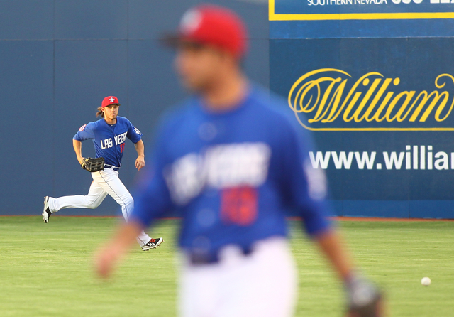 Las Vegas 51s' Matt den Dekker runs for a ball from Salt Lake Bees' Tommy Field, not pictured, during a baseball game at Cashman Field in Las Vegas on Tuesday, July 1, 2014. (Chase Stevens/Las Veg ...