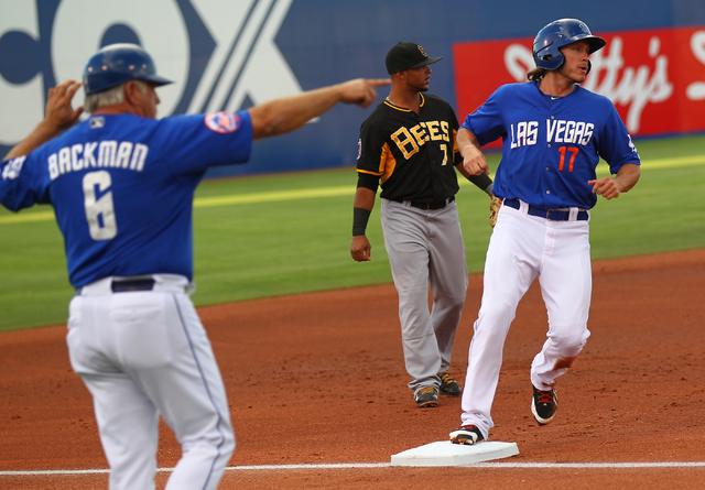 Las Vegas 51s' Matt den Dekker (17) arrives at third base as Manager Wally Backman (6) signals as the team takes on the Salt Lake Bees during a baseball game at Cashman Field in Las Vegas on Tuesd ...