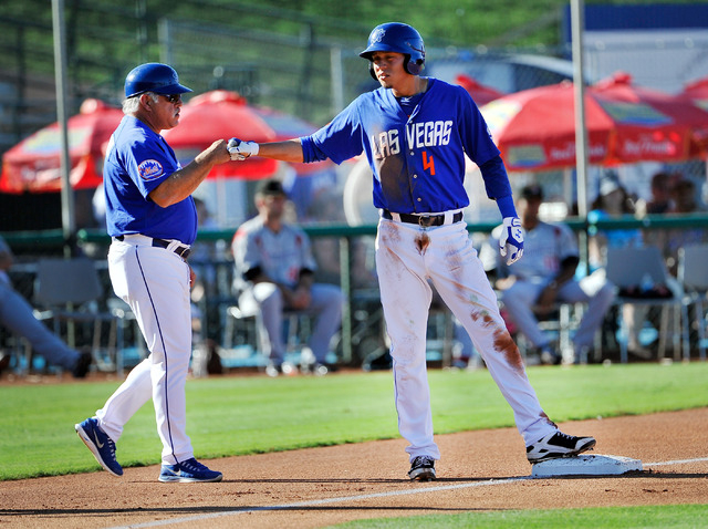 Las Vegas 51s' Wilmer Flores, right, gets a fist bump from manager Wally Backman after sliding into third base during a baseball game against the Albuquerque Isotopes at Cashman Field on Friday, J ...