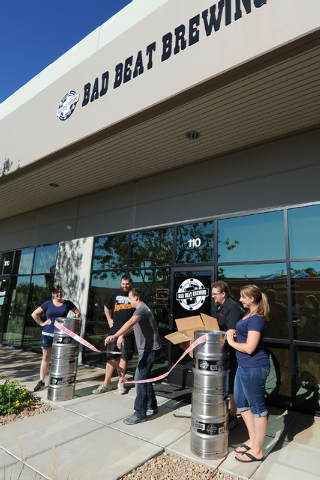 Owner Nathan Hall, center, cuts a ribbon made up of playing cards to signify the grand opening at Bad Beat Brewing in Henderson, Friday, July 11, 2014. The brew house opened on Friday to large cro ...