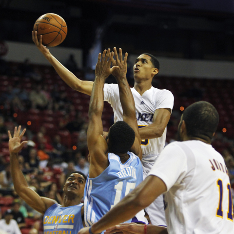 The Lakers' Jordan Clarkson (5) drives to the basket past Denver's Gary Harris (14) and Carlon Brown (15) during their NBA Summer League consolation round game at the Thomas & Mack Center in Las V ...