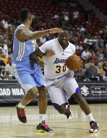 The Lakers' Julius Randle (30) drives past Denver's Jerelle Benimon (20) during their NBA Summer League consolation round game at the Thomas & Mack Center in Las Vegas on Friday, July 18, 2014. (J ...