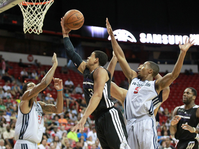 Sacramento's Ray McCallum (3) goes up for a shot between Washington's Jarell Eddie (21) and Kwame Vaughn (5) during an NBA Summer League semifinal game at the Thomas & Mack Center in Las Vegas on  ...
