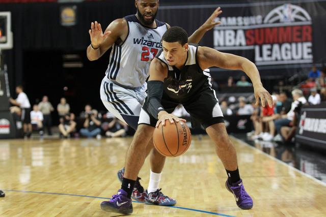 Sacramento's Ray McCallum (3) drives the ball against Washington's Deonte Burton (27) during an NBA Summer League semifinal game at the Thomas & Mack Center in Las Vegas on Sunday, July 20, 2014.  ...