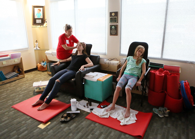 From left, Connie Thompson gives a scalp massage to Julia Munson and Erica Leavens during a sensory treatment session at the summer camp at the Nevada Blind Children's Foundation, June 26. (Ronda  ...