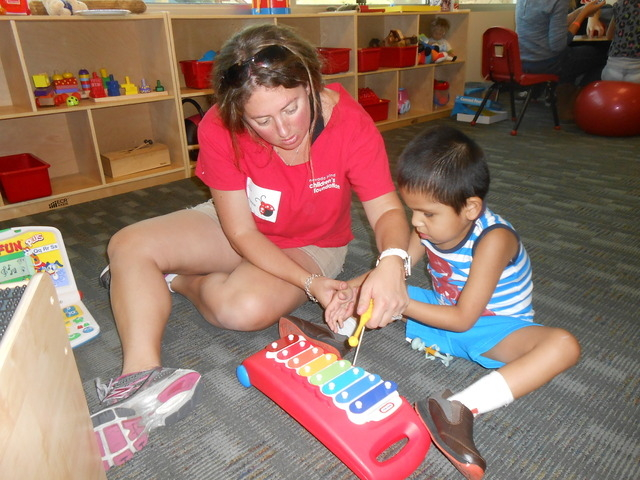 Suzanne Feigenson assists Angel Cordoba as he plays the xylophone during summer camp June 23 at the Nevada Blind Children's Foundation. The foundation's camp used tactile toys for the young chil ...