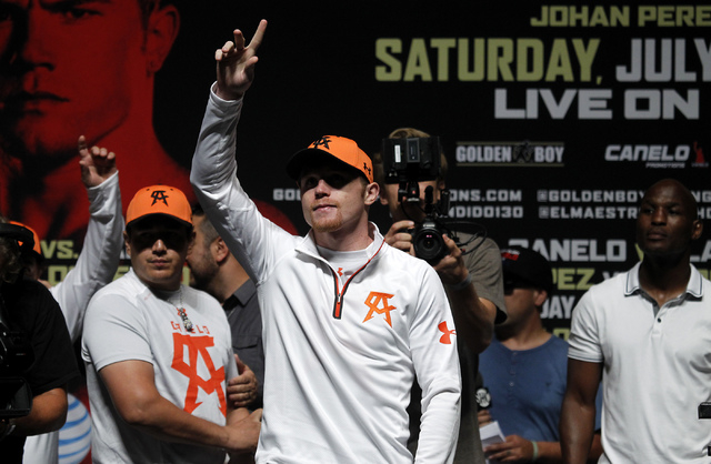 Boxer Saul Canelo Alvarez acknowledges the crowd during the official weigh in for his upcoming fight against Erislandy Lara at the MGM Grand Garden Arena in Las Vegas on Friday, July 11, 2014.(Jas ...