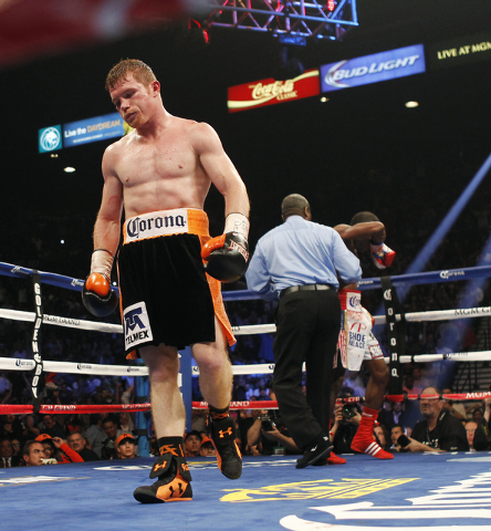 Saul Canelo Alvarez walks away after knocking down Erislandy Lara during the ninth round of their Super Welterweight fight at the MGM Grand Garden Arena in Las Vegas on Saturday, July 12, 2014.(Ja ...