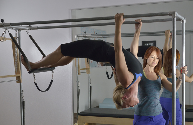 Juliet Lauren Clingan, owner of The Pilates Firm, right, works with student Melissa Roche during a demonstration at the studio at 8359 W. Sunset Road in Las Vegas on Friday, June 20, 2014. (Bill H ...