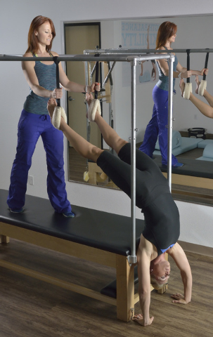 Juliet Lauren Clingan, owner of The Pilates Firm, left, works with student Melissa Roche during a demonstration at the studio at 8359 W. Sunset Road in Las Vegas on Friday, June 20, 2014. (Bill Hu ...