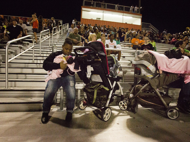 """Dajee Hill with her 2-week-old daughter Nehemiah during a Chaparral High School football home game against Faith Lutheran on Friday, Sept. 12, 2013. Her boyfriend James """"Bubba"""" Dukes plays for Cha ..."""