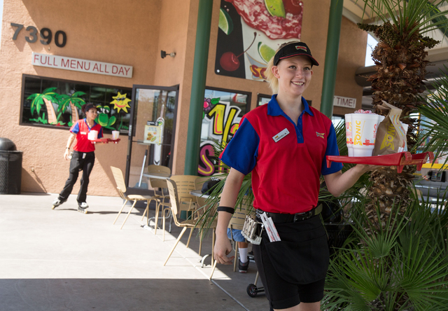 Sonic Drive-In's carhop Angela Galindo, right, delivers food to a car at the 7390 W. Cheyenne Ave. location Friday, July 11, 2014. (Samantha Clemens-Kerbs/Las Vegas Review-Journal)