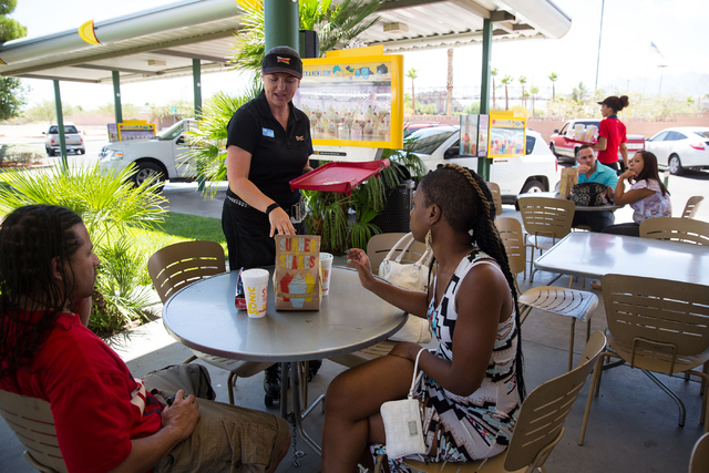 Sonic Drive-In's assistant manager Cherii Manthe (cq) delivers food to Beet Salaam (cq), left, and Malikah Washington (cq) at the 7390 W. Cheyenne Ave. location Friday, July 11, 2014. (Samantha Cl ...
