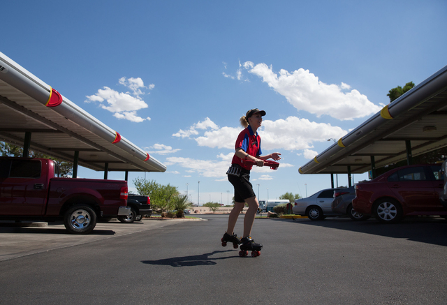 Sonic Drive-In's carhop Angela Galindo delivers food to a car at the 7390 W. Cheyenne Ave. location Friday, July 11, 2014. (Samantha Clemens-Kerbs/Las Vegas Review-Journal)