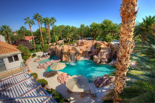 Courtesy photo Gary Primm designed the pool after a Hawaiian resorts. It is near the company's main residence has a water slide and spa. A walkway behind a waterfall that cascades out of a mock ma ...