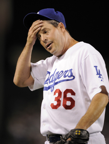 Los Angeles Dodgers' Greg Maddux wipes his head after errors by Rafael Furcal during the fifth inning in Game 5 of the National League baseball championship series agains the Philadelphia Phillies ...
