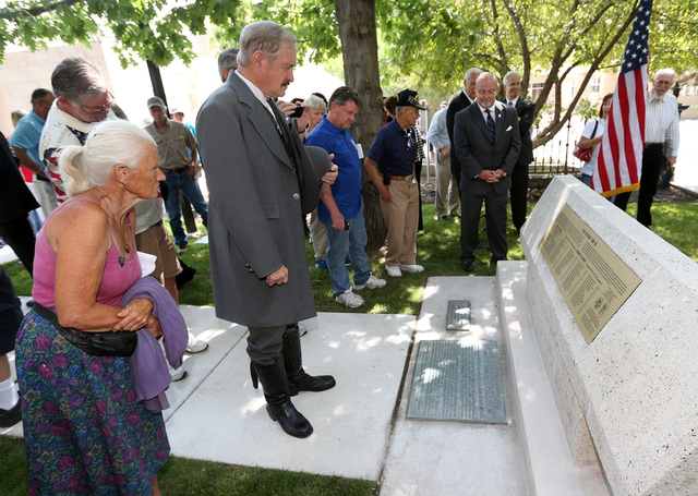 Supporters view a new plaque that was unveiled on the USS Nevada memorial following a ceremony honoring the Centennial of Launch at the Capitol, in Carson City, Nev., on Friday, July 11, 2014. (Ca ...