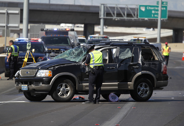 A Nevada Highway Patrol officer looks at a sport utility vehicle that was involved in a rollover accident on northbound Interstate 15 just south of the D Street exit in Las Vegas on Wednesday, Jul ...