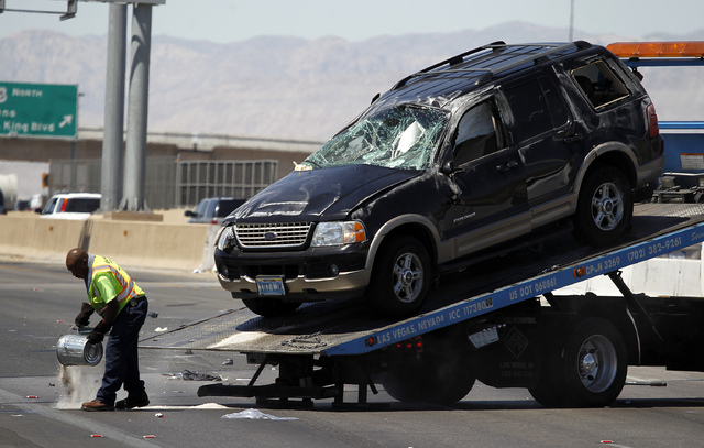 A Nevada Highway Patrol officer looks at an sports utility vehicle that was in an accident in which seven passengers were involved just south of the D Street exit on Northbound I-15 in Las Vegas o ...
