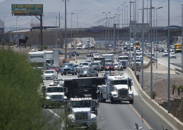 A tractor-trailer lays on its side blocking access to the 215 freeway on I-15 in Las Vegas on Wednesday, July 30, 2014. (Justin Yurkanin/Las Vegas Review-Journal)