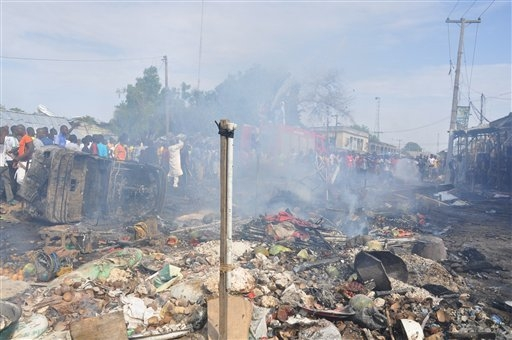 People gather at the scene of a car bomb explosion, at the central market, in Maiduguri, Nigeria, Tuesday, July 1, 2014. A car bomb exploded in a market in Nigerias northeastern city of Maiduguri  ...