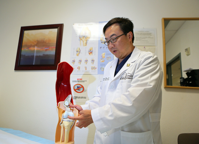 Dr. Thomas Kim points to a model of a knee at Nevada Orthopedic and Spine Center Wednesday, July 9, 2014, in Las Vegas. Kim performs surgery on young athletes with a torn anterior cruciate ligamen ...