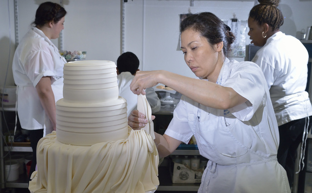 Van Trinh works on a wedding cake being made to mimic the folds, bows and beading on the bride's dress at Freed's Bakery at 9815 S. Eastern Ave. in Las Vegas on Thursday, July 3, 2014. (Bill Hughe ...