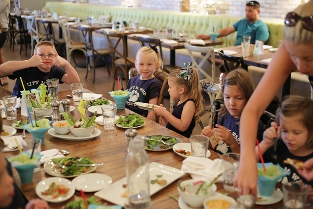 Students from Kitty Ward Elementary School sample items created with garden ingredients, June 30. (Special to View)