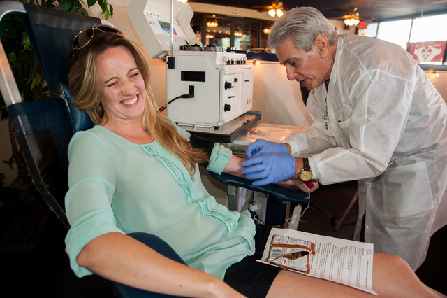 Erin Booth, left, of Las Vegas prepares to give blood as United Health Services phlebotomist James Lee inserts a needle to draw blood during the National Gay Blood Drive held at the Blue Ox Tavern ...