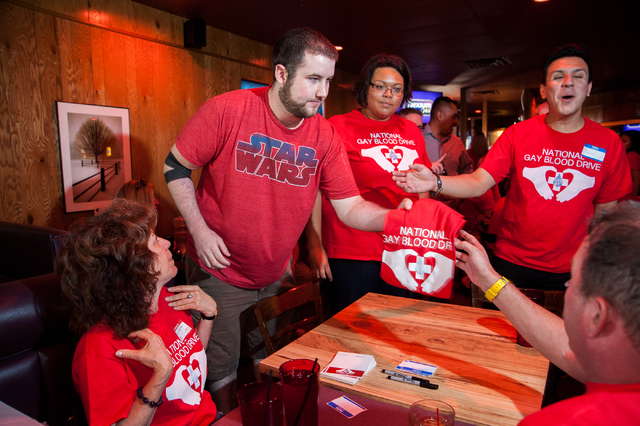 Garrett Greenblatt, second from left, is given a t-shirt for donating his blood during the National Gay Blood Drive held at the Blue Ox Tavern at 5825 W. Sahara Ave. in Las Vegas on Friday, July 1 ...