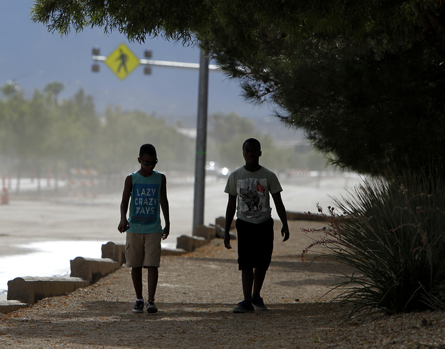 Two boys walk along Grand Teton drive in Las Vegas on Monday, July 7, 2014. The boys were trying to go to the park but couldn't cross the road because of high flood waters. (Justin Yurkanin/Las Ve ...