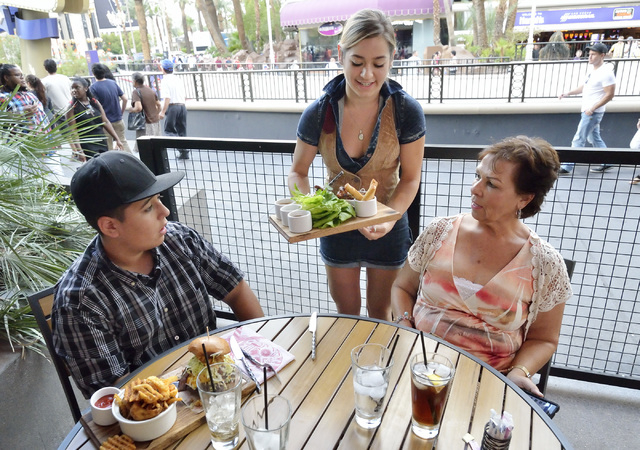 Brandy Nunez, center, serves Andrew Singh, left, and his grandmother Pam Ramirez at Guy Fieri's Vegas Kitchen and Bar in the Quad hotel-casino at 3535 Las Vegas Blvd., South, in Las Vegas on Satur ...