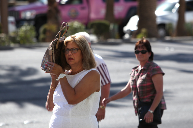 A tourist uses her purse to shield herself from the sun on Las Vegas Boulevard in Las Vegas on Tuesday, July 1, 2014. An excessive heat watch was issued for the valley as temperatures topped 110 d ...
