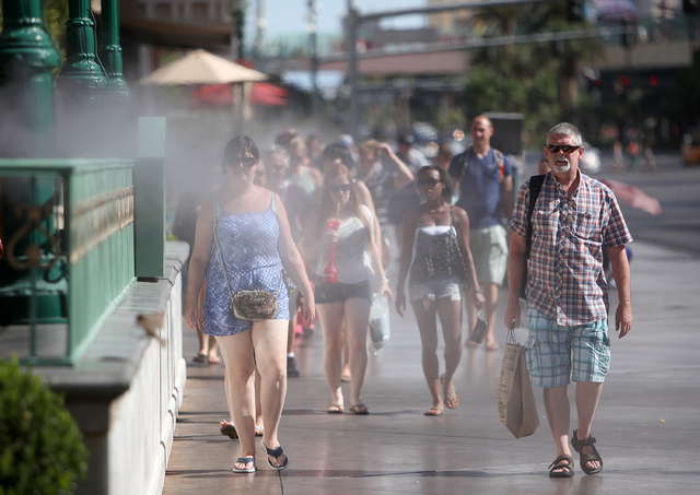 Tourists walk through misters along Las Vegas Boulevard in Las Vegas on Tuesday, July 1, 2014. An excessive heat watch was issued for the valley as temperatures topped 110 degrees on Tuesday. (Jus ...