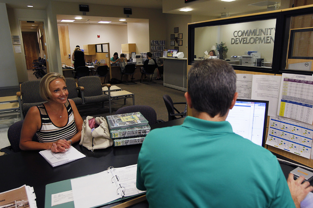 Debra Freeman, left, is helped by city employee Scott Majewski while applying for a medical marijuana establishment in the Community Development office at Henderson City Hall on July 17, 2014. (Ja ...