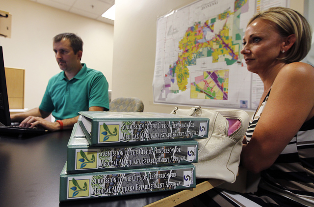 Debra Freeman, right, is helped by city employee Scott Majewski while applying for a medical marijuana establishment in the Community Development office at Henderson City Hall on July 17, 2014. (J ...