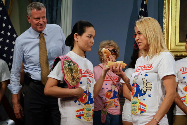 New York City Mayor Bill de Blasio watches hot dog eating contestants Sonya Thomas, left, and Miki Sudo during a news conference to promote Friday's Nathan's Famous Fourth of July Hot Dog Eating C ...