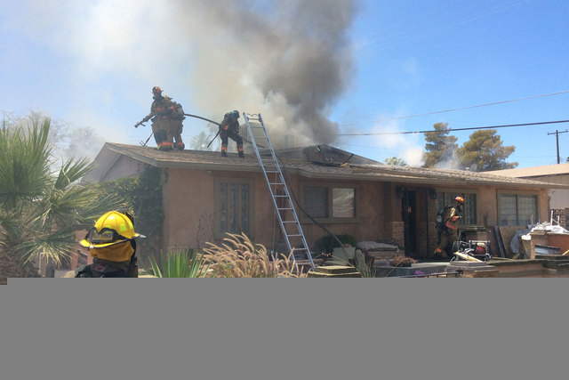 The Las Vegas Fire Department battles a house fire that started about noon Thursday at 3013 Merritt Ave., near West Sahara Avenue and North Valley View Boulevard. Two people were taken to the hosp ...