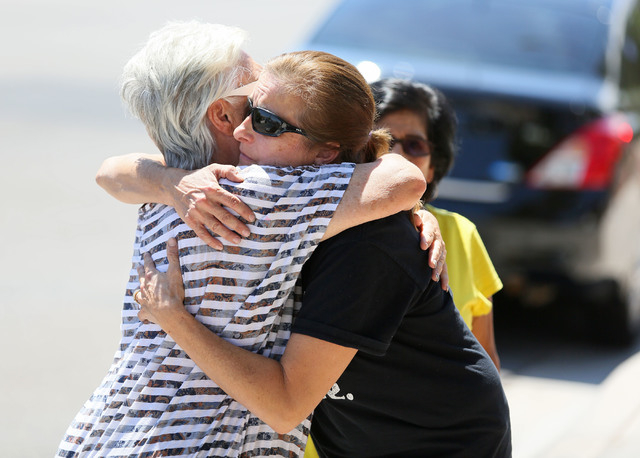 Julie Ramos, center right, is comforted by her neighbor Vita Hawkins outside Ramos' home prior to a news conference on Autumn Street Wednesday, July 30, 2104, in Las Vegas. The Ramos family ...